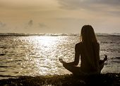 Silhouette Of Woman Making Meditation Near The Ocean