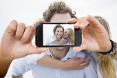 Hand holding smartphone showing man piggybacking woman at beach