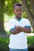 Little boy frowning at camera with arms crossed in the park on a sunny day