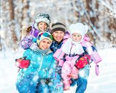 Winter portrait of happy young family of 4 people