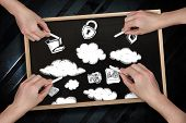 Composite image of multiple hands drawing clouds with chalk on blackboard