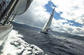Sailing yachts in the sea at race in stormy weather.
