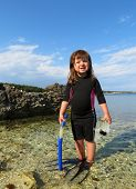 portrait of happy young girl with wetsuit at the sea