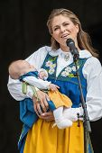 Princess Madeleine Of Sweden With Princess Leonore In Her Arms Having A Public Speach