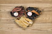 Old Baseball Gloves And Balls On Aged Wood