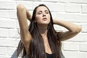 Beautiful sexy young brunette on white brick wall