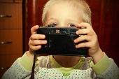 Young Child With A Camera In Hand.