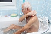 image of bath sponge  - Senior man washing his body with soap sponge in bath - JPG