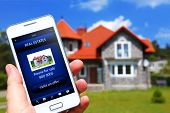hand holding mobile phone with house sale offer