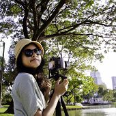 Girl With Camera In Public Park
