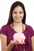 Portrait Of Young Woman Holding A Piggy Bank