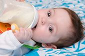stock photo of teats  - Six month old baby drinking milk from a bottle with the teat - JPG