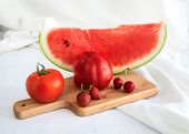 Water Melon, Tomatoes, Strawberries And Cherries On Wooden Background And White Fabric