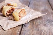 Tasty homemade apple strudel  on paper napkin, on wooden background