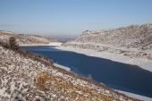 stock photo of horsetooth reservoir  - Horsetooth Reservoir in Colorado with highway and view of Fort Collins and plains over a dam winter scenery with snow and still unfrozen water - JPG