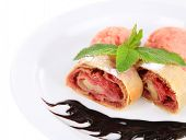 Tasty homemade strudel with ice-cream, chocolate sauce and mint leaves isolated on white