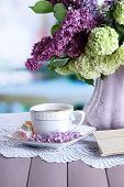 Composition with  cup of tea, old letters and beautiful spring flowers in vase, on wooden table, on bright background