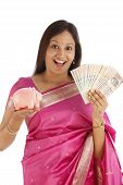 Surprised Young Indian Traditional Woman Holding Currency And Piggy