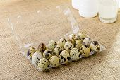 picture of quail egg  - Quail eggs in a transparent plastic container on a burlap tablecloth - JPG