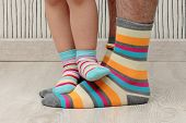 stock photo of stocking-foot  - feet of a beautiful father and daughter with striped socks - JPG