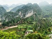 Vietnamese village among rice fields and limestone rocks at the early morning. Ninh Binh Vietnam