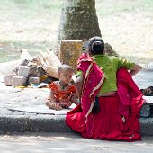 Indian woman in sari takes care about her baby