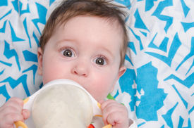 foto of teats  - Six month old baby drinking milk from a bottle with the teat - JPG