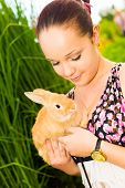 Young Woman Smiling And Holding Cute Rabbit