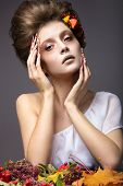 Beautiful girl in autumn image with long nails with bright and unusual make-up.