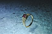 gold ring with red ruby on water drop blue background