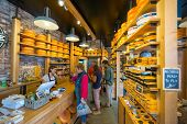 AMSTERDAM - AUGUST 29: Cheese wheels are on the shelves in the store on August 29, 2014 in Amsterdam.
