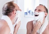 Expressed Young Man Shaving Near The Mirror