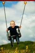 Little boy having fun at the playground. Child playing on a swing outdoor. Happy active c