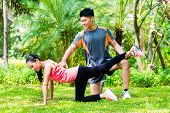 Asian Chinese personal trainer helping woman with stretching exercises in park