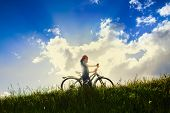 Young woman with bicycle standing over sunbeams on blue sky