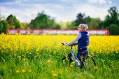 Young woman with bicycle enjoying view of yellow rapeseed field and passing train