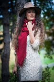 smiling young woman wearing hat,  red wool scarf and wool dress enjoy in autumn  day outdoor shot in forest