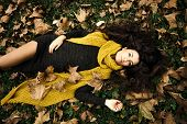 beautiful woman  lie in grass and autumn leaves wearing dark green dress and long yellow wool scarf