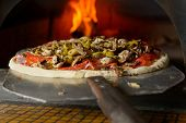 Fresh original Italian pizza on a shovel is putting in a traditional wood-fired stone oven.
