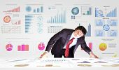 Young businessman and statistics information at background