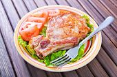 foto of shoulder-blade  - fried meat with salad on plate and on a table - JPG