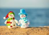 Two snowman on sand near sea. Christmas decoration. Vacations