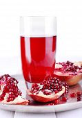 Ripe pomegranate and glass of juice on white wooden table