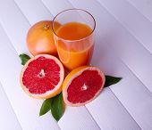 Grapefruit juice and fresh grapefruit on wooden table