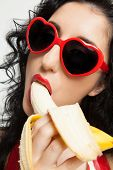 Beautiful woman with red sunglasses sexy eating banana