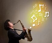 Handsome young musician playing on saxophone with musical notes
