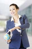 Young business woman holding small globe
