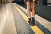 Detail of a young woman's legs posing in a metro station