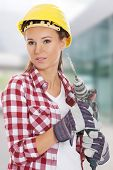 Young woman in protective helmet and jackhammer