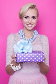 Beautiful blonde woman with cream dress giving colorful gift